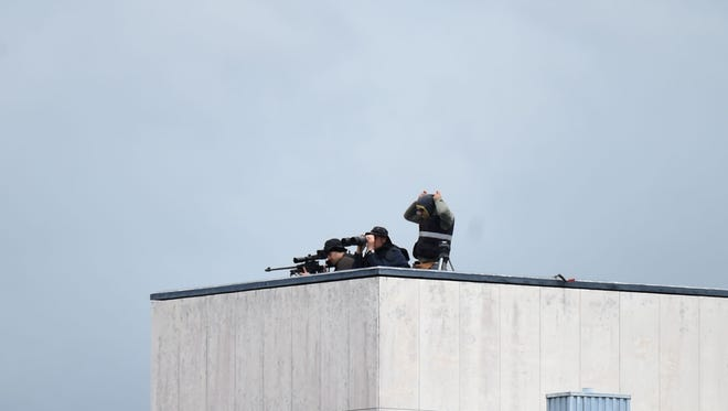 A sniper and his observer watch from a rooftop.