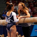 Penn State's coach Rachelle Thompson talks with a gymnast before a balance beam routine in 2014.