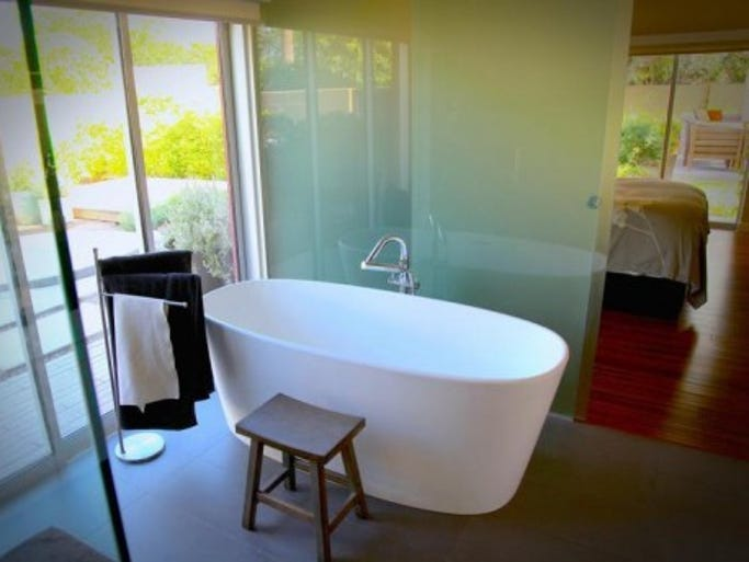 At Jim and Luisana Idsardi's home in Paradise Valley, architect Cathy Hayes used floor-to-ceiling panels of frosted glass to separate the ensuite baths from the bedrooms.