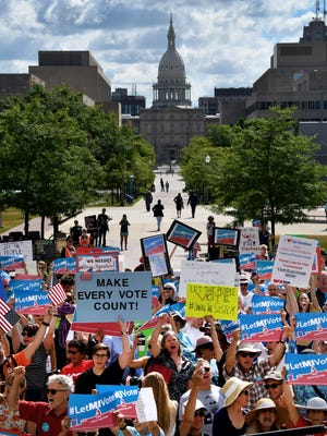Over 100 demonstrators rally outside the Michigan Hall of Justice Wednesday, July 18, 2018, where the Michigan Supreme Court heard arguments on whether the constitution should be amended by voters to change the way political districts are made. The Capitol is visible in the background.