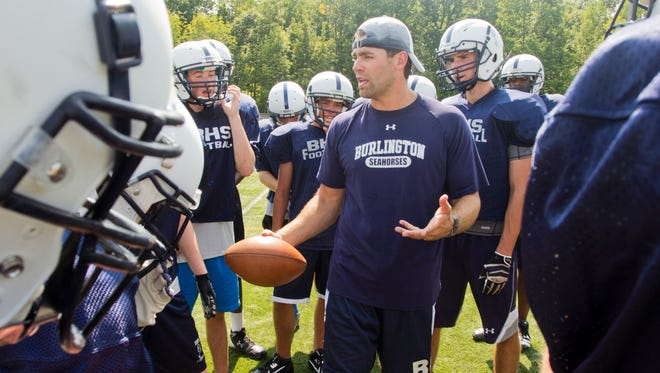 Coach Brennan Carney talks with players during Burlington High School's first day of football practice Monday.