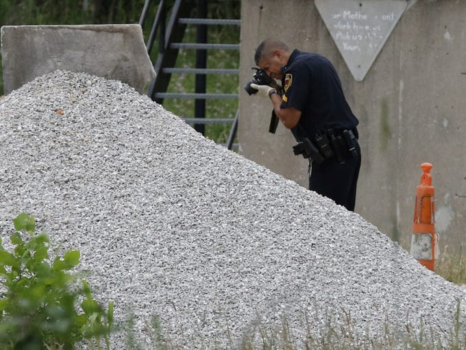An officer photographs evidence in a shooting scare