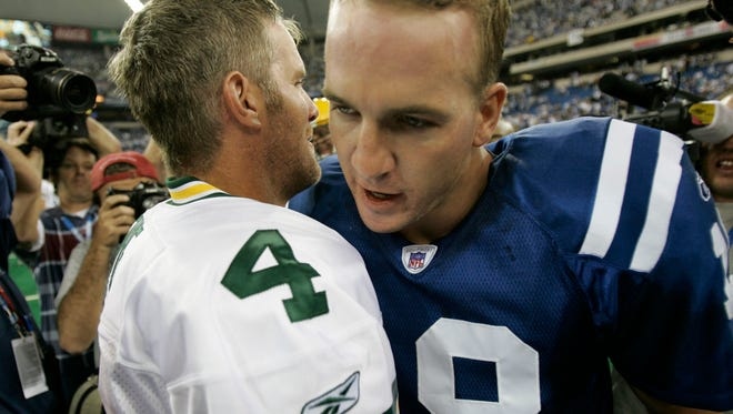 Green Bay Packers quarterback Brett Favre and Indianapolis Colts quarterback Peyton Manning embrace following their game at the RCA Dome in Indianapolis in September 2004.