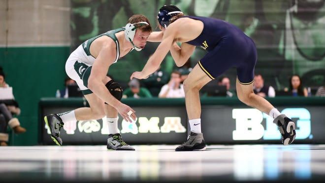 Former Hartland wrestling star and current Michigan State 133-pounder Austin Eicher (left) will compete in the NCAA Championships beginning Thursday.