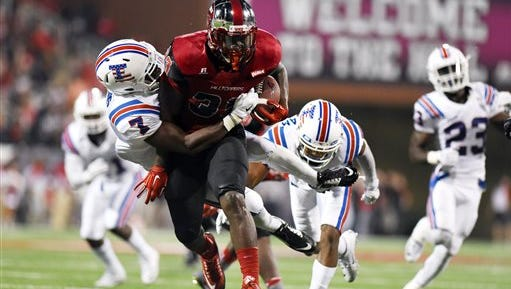 Western Kentucky's De'Andre Simmons (23), right, its tackled by Louisiana Tech's Xavier Woods (7) in the first half of an NCAA college football game Thursday, Sept. 10, 2015, in Bowling Green, Ky. (AP Photo/Michael Noble Jr.)