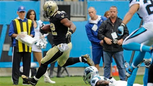 New Orleans Saints' Mark Ingram (22) runs past Carolina Panthers' Josh Norman (24) for a touchdown in the first half of an NFL football game in Charlotte, N.C., Sunday.