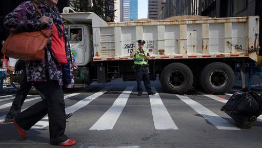 """In this Sept. 24, 2015 file photo, a police office stands guard at a loaded dump truck that serves as a barricade along the perimeter of St. Patrick's Cathedral before the arrival of Pope Francis in New York. More than 80 city sanitation trucks will be used at intersections and other strategic spots along the 2.5 mile Macy's Thanksgiving Day parade route to create an imposing physical barrier to terror. """"You can ram a New York City Sanitation Department sand truck with a lot of things, but you're not going to move it,"""" said John Miller, the New York Police Department's top counter-terrorism official."""