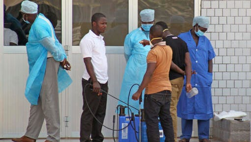 FILE - In this March 29, 2014, file photo, medical personnel at the emergency entrance of a hospital wait to receive suspected Ebola virus patients in Conakry, Guinea. Final test results confirm an experimental Ebola vaccine is highly effective, a major milestone that could help prevent the spread of outbreaks like the one that killed thousands in West Africa. (AP Photo/Youssouf Bah, File)