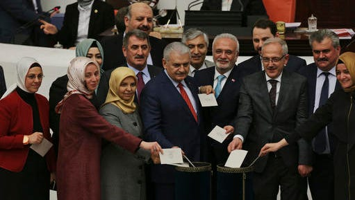 Turkey's Prime Minister, Binali Yildirim, centre, accompanied by some of his lawmakers cast their votes following Turkey's parliament debate proposing amendments to the country's constitution that would hand President Recep Tayyip Erdogan's largely ceremonial presidency sweeping executive powers, in Ankara, Turkey, Friday, Jan. 20, 2017.