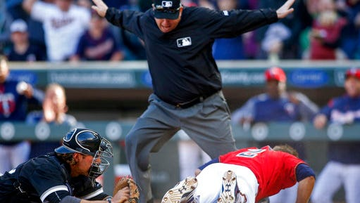 Umpire Todd Tichenor calls Minnesota Twins Brian Dozier safe on an inside the park home run after Chicago White Sox catcher Kevan Smith tried to tag him in the fifth inning of a baseball game Sunday, April 16, in Minneapolis.