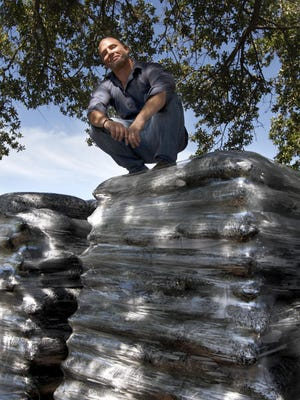 Patrick Hesser, general manager of Allied Prefer LLC, on top of Mulch-Less, a mulch product made from invasive species, mostly melaleuca, at the manufacturing facility Thursday in Fort Myers.