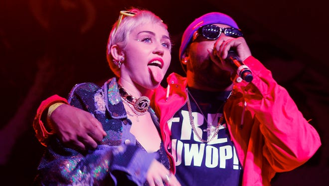 Miley Cyrus, left, joins Mike Will Made It onstage at the Fader Fort Presented by Converse during the SXSW Music Festival on Thursday, March 19, 2015 in Austin, Texas.