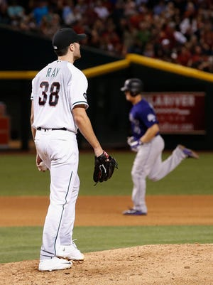 Arizona Diamondbacks' Robbie Ray (38) walks back to the mound after giving up a home run to Colorado Rockies' Nick Hundley, right, during the fourth inning of a baseball game Friday, April 29, 2016, in Phoenix.
