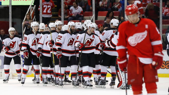 Devils players celebrates their 4-3 win against the Red Wings on Tuesday in Detroit.