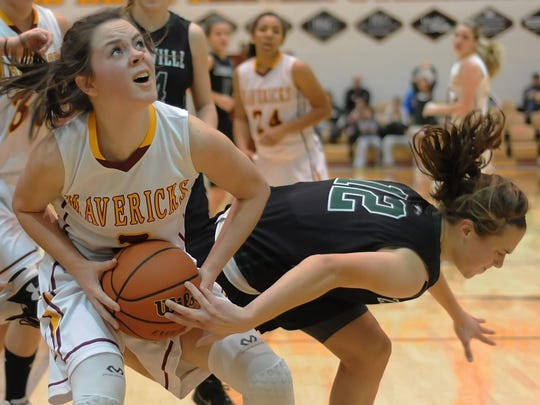 McCutcheon junior Hunter Carmony fights for the ball under the basket against Zionsville's Erin Patterson.