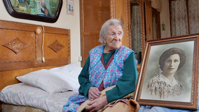 Emma Morano sits in her apartment next to a picture of her where she was young in Verbania, northern Italy on Friday. The 116-year-old woman from the northern Italian region of Piedmont, became the world's oldest person following the death of the previous holder of the record, New York CIty's Susannah Mushatt Jones, who passed away in Brooklyn on Thursday.