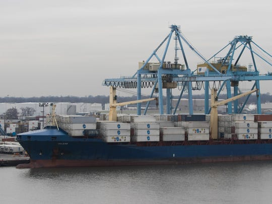 Chiquita shipping containers are loaded and unloaded from a waiting cargo ship at the Port of Wilmington Wednesday.