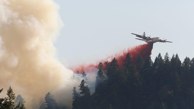 A plane drops flame retardant on a wildfire near Milo, Ore., Thursday, July 30, 2015. (Michael Sullivan/The News-Review via AP) MANDATORY CREDIT