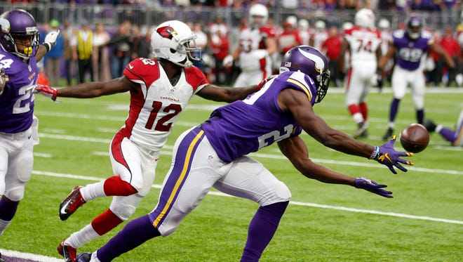 Minnesota Vikings cornerback Xavier Rhodes, right, intercepts a pass in the end zone in front of Arizona Cardinals wide receiver John Brown (12) during the first half of an NFL football game Sunday, Nov. 20, 2016, in Minneapolis. Rhodes returned the interception 100-yards for a touchdown.