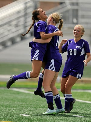 Wylie's Randie Dennison (10) celebrates with teammates Jessica Boldenow (16) and Kaleigh Wilson (20) after a goal in the second half of the Lady Bulldogs' 2-0 win in the Region I-4A semifinal on Friday, April 8, 2016, at Wildcat Stadium in Kennedale.