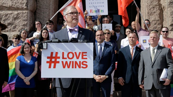 Jim Obergefell, the named plaintiff in the Obergefell v. Hodges Supreme Court case that legalized same sex marriage nationwide, is backed by supporters of the courts ruling on same-sex marriage on the step of the Texas Capitol during a rally Monday, June 29, 2015, in Austin, Texas. The Supreme Court declared Friday that same-sex couples have a right to marry anywhere in the United States. (AP Photo/Eric Gay) ORG XMIT: TXEG112