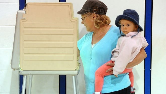 Diane Middleton holds her granddaughter Madi Medius while she votes at the District Education Center in Tea on Tuesday, Oct. 14, 2014.