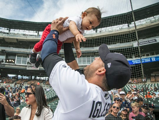 Detroit Tigers' Jose Iglesias holds up his 9-month-old