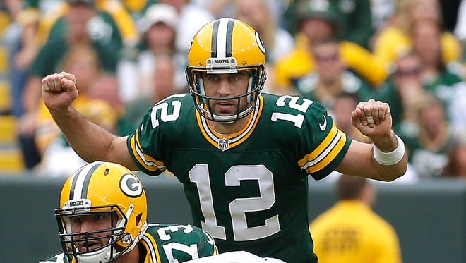 Green Bay Packers quarterback Aaron Rodgers (12) signals a play during the Green Bay Packers' 34-27 win over the Detroit Lions  last month.