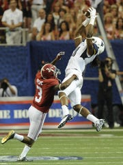 West Virginia wide receiver Kevin White catches a pass over Alabama defensive back Bradley Sylve.