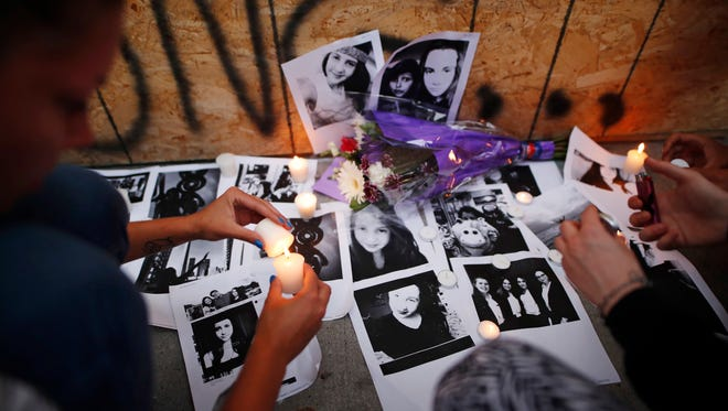 People light candles and leave photos of 18-year-old victim Reese Fallon at a memorial remembering the victims of a shooting in Toronto.