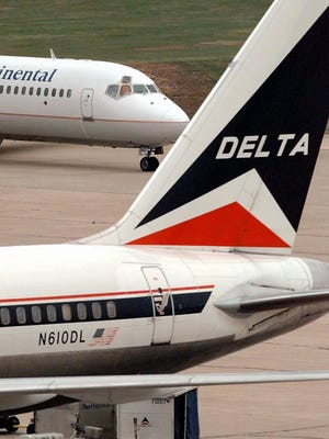 A Continental Airlines jet passes behind a Delta Airlines plane parked at a gate at Houston Intercontinental Airport Wednesday, Dec. 4, 1996, in Houston.