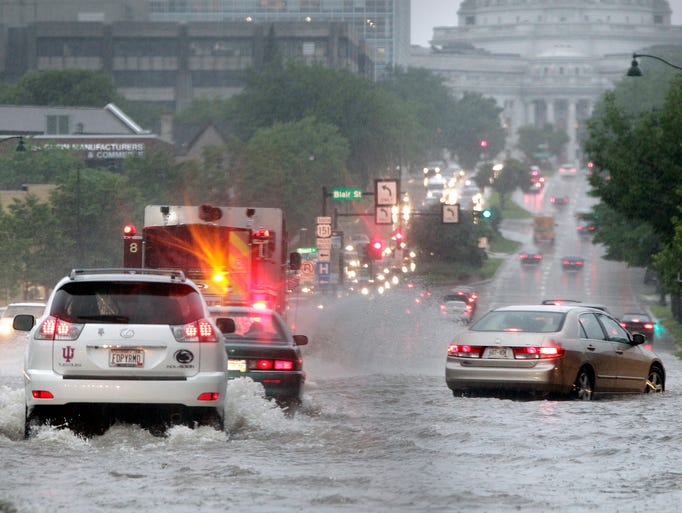 Motorists and a fire engine brave high water on East Washington Avenue approaching the state Capitol building after a strong storm dumped large amounts of rain in Madison, Wis., Monday, June 30, 2014. (AP Photo/Wisconsin State Journal, M.P. King)