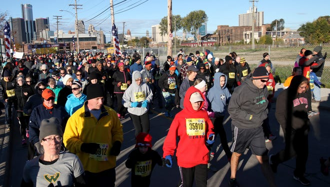 Crowds run down Atwater Street right after the start of the American Home Fitness 5K in Detroit, Michigan on Sat., Oct. 17, 2015. This race is part of the Detroit Free Press/Talmer Bank Marathon weekend in Detroit.