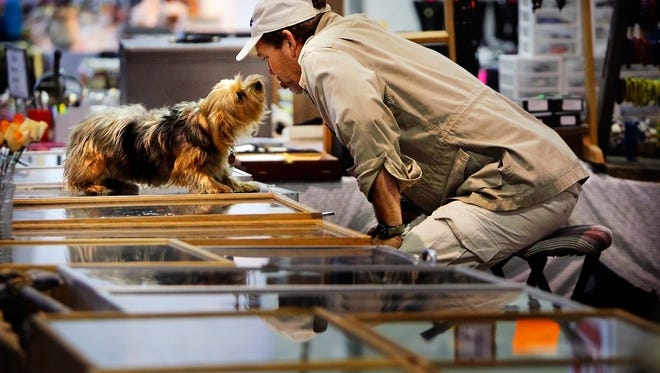 Dec 4, 2011 - Wayne Caldwell plays with his dog Cleo while waiting for customers to browse his selection of knives during the Big One Flea Market at the Agricenter. The Big One will be returning to the fairgrounds in Midtown Memphis in time for the January show.