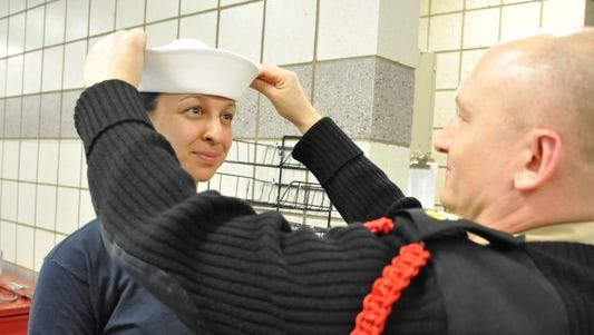"Chief Boatswain's Mate Ludwik Dyrkacz, a recruit division commander, ensures the proper fit of Seaman Recruit Madeleine Bohnert's white enlisted hat, or ""Dixie cup,"" on April 4 during uniform issue at Recruit Training Command."