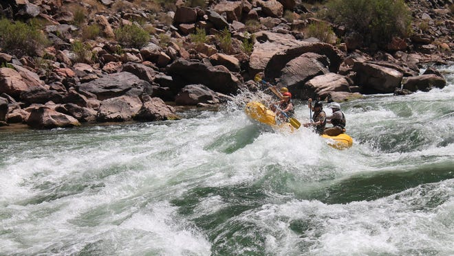 With gear safely tied down in 18-foot, two-person rafts, William Salaun and members of the group make their way through the cold rapids of the Colorado River.