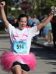 Judy Slaugh celebrates after finishing the Susan G. Komen Southwest Florida Race for the Cure at Coconut Point. Slaugh was running for cancer survivor Maxine Bond. photos by jack hardman/the news-press Judy Slaugh celebrates after finishing the Susan G. Komen Southwest Florida Race for the Cure at Coconut Point. Slaugh was running for cancer survivor Maxine Bond.