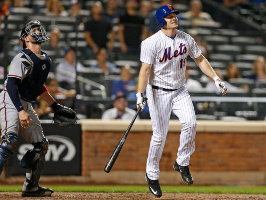 Atlanta Braves catcher Tyler Flowers, left, watches as New York Mets' pinch hitter Jay Bruce (19) winces after flying out to right field in the ninth inning of a baseball game Monday, Sept. 19, 2016, in New York. The Braves defeated the Mets 7-3. (AP Photo/Kathy Willens)