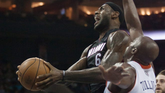 Miami Heat small forward LeBron James (6) goes up for a shot while Charlotte Bobcats power forward Anthony Tolliver (43) defends during the first half at Time Warner Cable Arena.