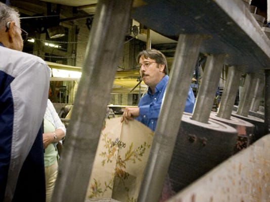 In this file photo, York Wallcoverings manager Steve Flohr shows a tour group a wallpaper sample near a rack of print rollers at the plant in York Wednesday. The business is part of the Made in America Tours, the popular event that offers free tours at area manufacturers, businesses and museums.