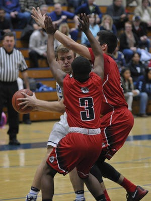 Redwood's Drew Stogsdill is double teamed by a pair of Hanford defenders on Wednesday in a West Yosemite League game at Redwood High School.