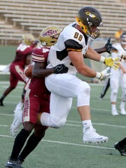 Midwestern State's Robert Grays hits Quincy's Owen Schoenenberger as the ball falls behind them in the opening game of the season Thursday, Aug. 31, 2017, at Memorial Stadium.