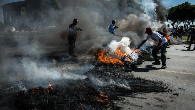 People burn tires and block access to the Estádio Nacional Mané Garrincha in Brasilia at the 2013 Confederations Cup.