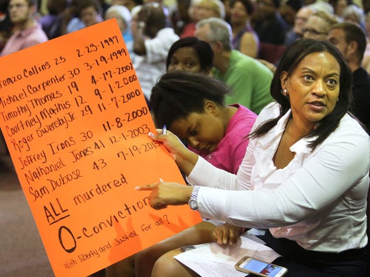 Kelli Prather, of Price Hill, holds up a sign during