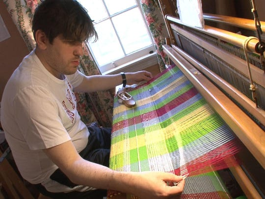 Brian Thorogood works the loom to make bags in the weaving program at OASIS.