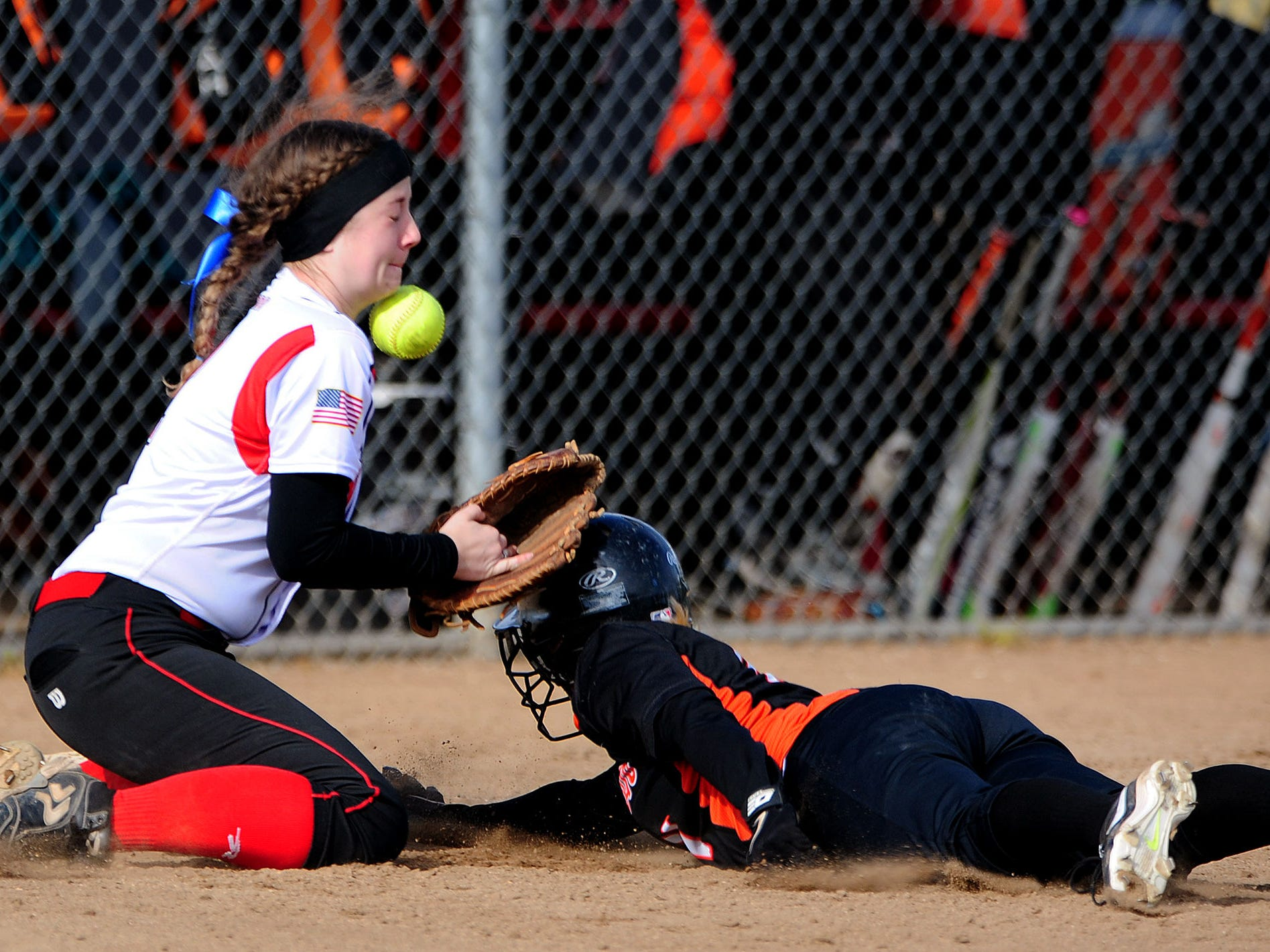 Central's Kaitlyn Noon has the ball bounce into her chin as Silverton's Dianne Allen slides safely back to first base during the first game of a doubleheader, on Friday, April 24, 2015, in Independence.