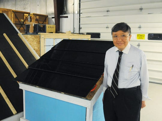 Frank Pao, chairman and CEO of Atlantis Energy Systems, stands next to a prototype of his latest solar panel in a Poughkeepsie factory where he collaborates with Bill James, CEO of JPods, Inc.