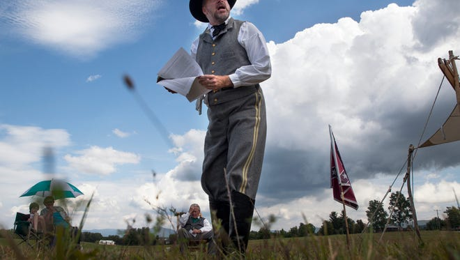 A Civil War reenactor delivers a sermon before the start of a battle reenactment to commemorate the 150th and 149th anniversaries of the first and second battles of Waynesboro at Coyner Springs Park on Sunday, Aug. 31, 2014.