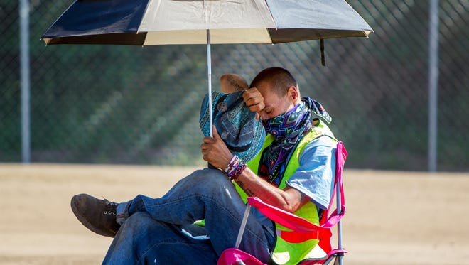 Dave Booczko wipes sweat off his forehead while directing traffic in the heat in Rothbuy, Mich., Friday, June 29, 2018.