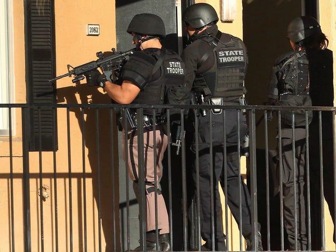 Law enforcement officers conduct a door-to-door search